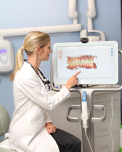 Dr. Julia pointing the screen that showing a simulation of teeth
